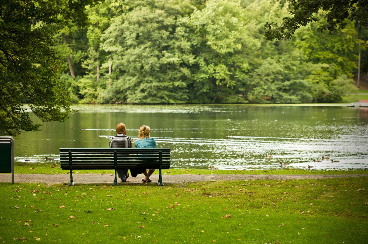 Couple sitting on bench next to lake